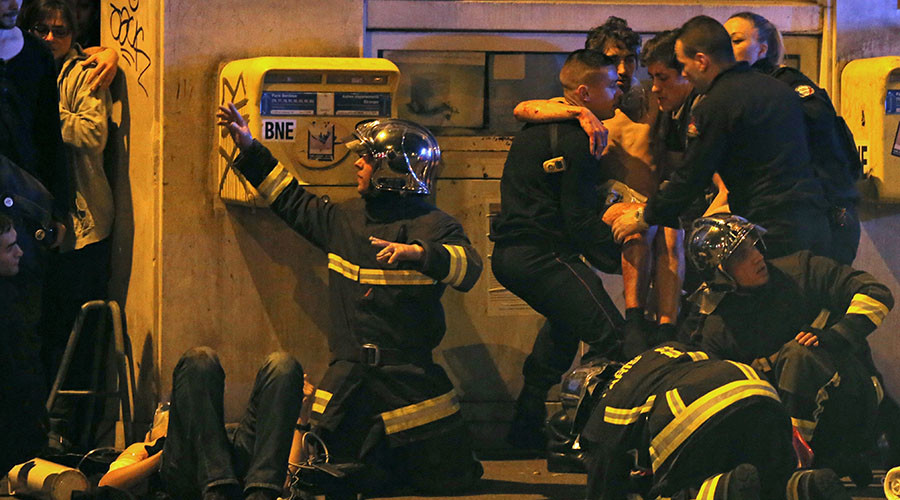 French fire brigade members aid an injured individual near the Bataclan concert hall following fatal shootings in Paris, France, November 13, 2015. © Christian Hartmann