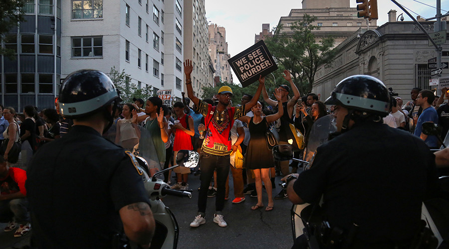 Protesters, marching against the killing of Alton Sterling and Philando Castile, hold placards towards members of the New York Police Department on motorbikes in Manhattan, New York, U.S., July 7, 2016 © Bria Webb
