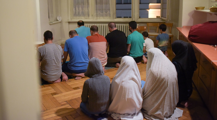 Migrants pray after the Iftar (breaking fast) meal at a refugee shelter in a former hotel in Berlin, Germany June 9, 2016. © Stefanie Loos