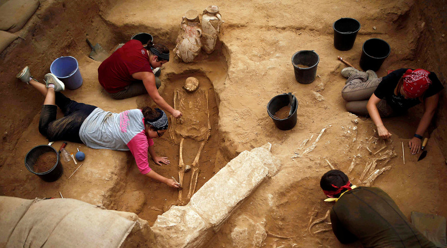 American archaeology students unearth a skeletons and clay jars during excavation works at the first-ever Philistine cemetery at Ashkelon National Park in southern Israel. © Amir Cohen