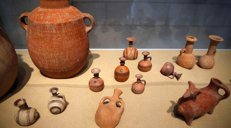 Clay items unearthed during excavations at the first-ever Philistine cemetery in Ashkelon National Park, are displayed at an exhibition in the Rockefeller Museum in Jerusalem. © Amir Cohen