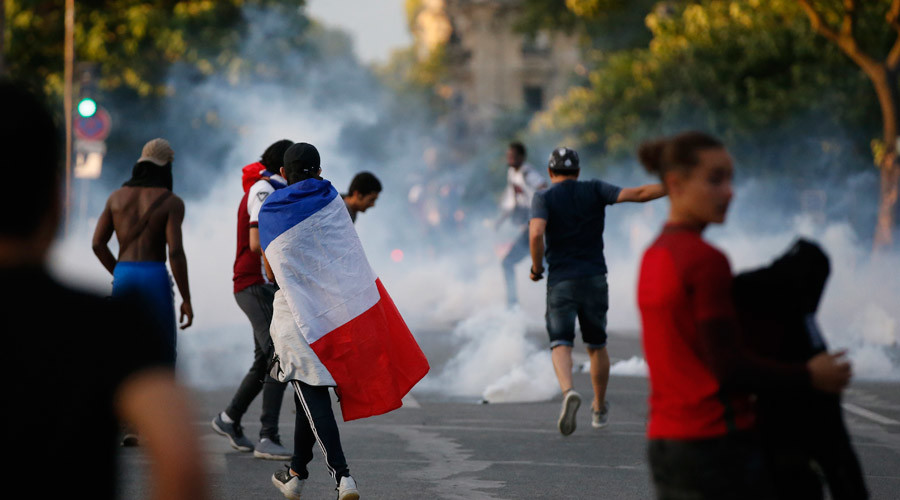 Tear gas floats in the air during clashes near the Paris fans zone during the Portugal v France EURO 2016 final soccer match, at the Eiffel Tower in Paris, France, July 10, 2016. © Stephane Mahe
