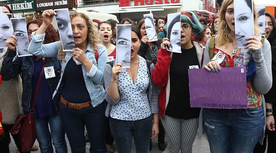 Turkish women display photographs of slain student, Özgecan Aslan, who was killed while resiting an attempted rape, and other victims of violence against women during a demonstration in Ankara on June 12, 2015. © Adem Altan