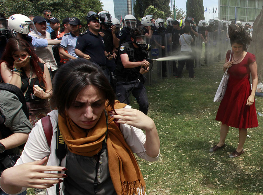 A Turkish riot policeman uses tear gas as people protest against the destruction of trees in a park brought about by a pedestrian project, in Taksim Square in central Istanbul in this May 28, 2013 file photo. © Osman Orsal