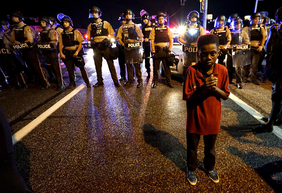 Amarion Allen, 11-years-old, stands in front of a police line shortly before shots were fired in a police-officer involved shooting in Ferguson, Missouri August 9, 2015. ©Rick Wilking