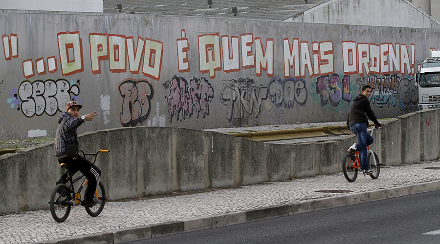 "A cyclist rides past graffiti that reads ""Power to the people"" on the streets of Lisbon. © Hugo Correia"