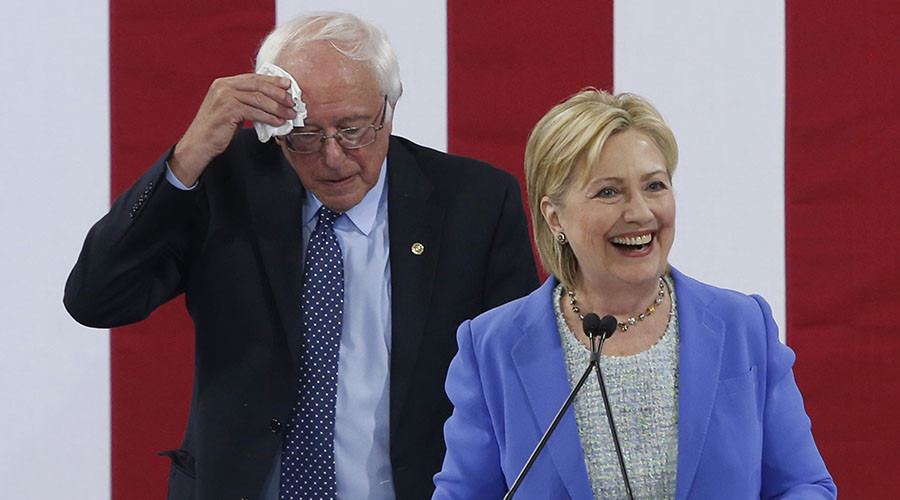 Democratic U.S. presidential candidate Hillary Clinton speaks as Senator Bernie Sanders wipes his brow after he endorsed her during a campaign rally in Portsmouth, New Hampshire, U.S., July 12, 2016. © Mary Schwalm