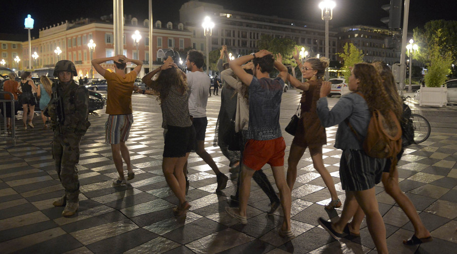 People cross the street with their hands on thier heads as a French soldier secures the area July 15, 2016 after at least 60 people were killed along the Promenade des Anglais in Nice, France, when a truck ran into a crowd celebrating the Bastille Day national holiday July 14. © Jean-Pierre Amet