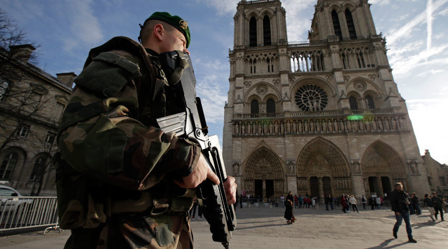 An armed French soldier patrols in front of Notre Dame Cathedral in Paris, France © Philippe Wojazer