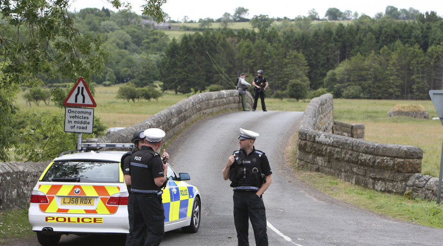 Police officers guard a bridge on the outskirts of Rothbury, northern England. © Nigel Roddis