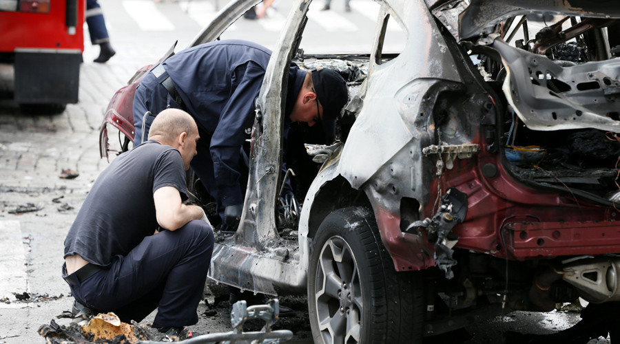 Investigators inspect a damaged car at the site where journalist Pavel Sheremet was killed by a car bomb in central Kiev, Ukraine, July 20, 2016. © Valentyn Ogirenko