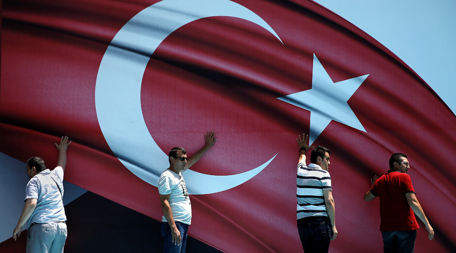 Men hold a stage background during a pro-government demonstration in Sarachane park in Istanbul © Alkis Konstantinidis