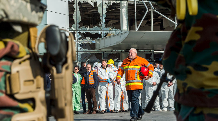 Staff members at Brussels airport and rescuers stand outside the terminal for a ceremony March 23, 2016. © Geert Vanden Wijngaert