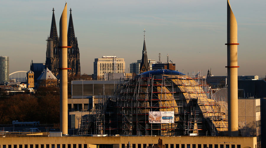 The two 55m high minarettes and the construction site of the new Cologne Central Mosque are seen next to the famous landmark and UNESCO world heritage, the Cologne Cathedral in Germany. © Wolfgang Rattay