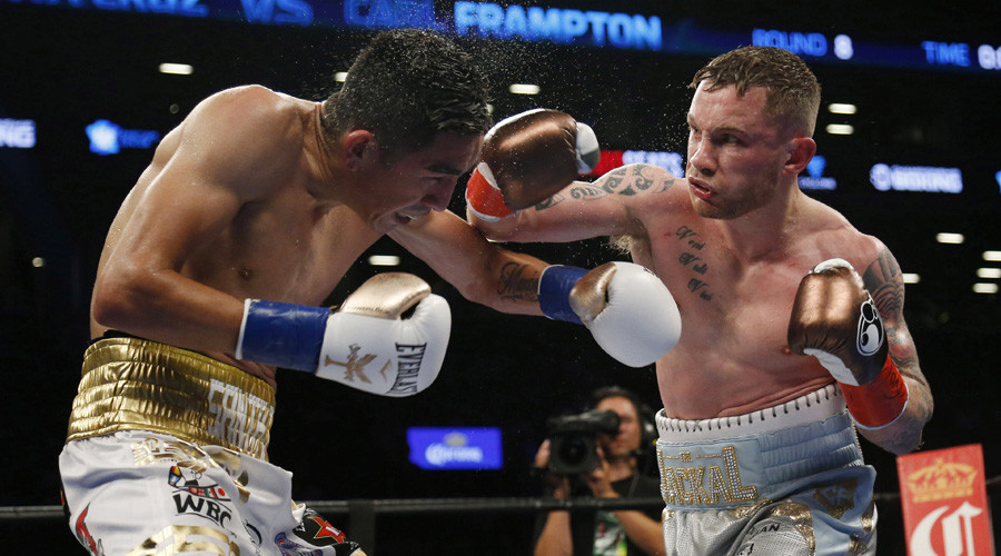 Carl Frampton lands a punch to Leo Santa Cruz during their WBA super world featherweight championship boxing match at Barclays Center. © Noah K. Murray