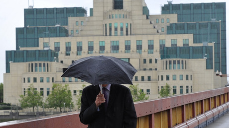 A man shields himself from the rain as he walks near the MI6 building in London © Toby Melville