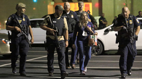 Dallas police officers escort a woman near the scene where eleven Dallas police officers were shot and five have now died on July 7, 2016 in Dallas, Texas. © Ron Jenkins