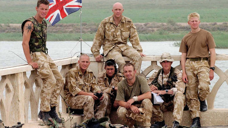 Unidentified Royal Marines sit with a British Union flag atop of Iraqi