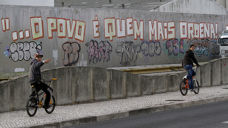 A cyclist rides past graffiti that reads