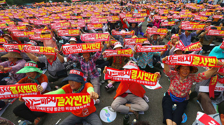 Thousands of South Korean residents hold up red banners reading