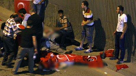 People react as bodies draped in Turkish flags are seen on the ground during an attempted coup in Ankara, Turkey July 16, 2016. © Stringer