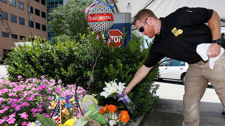 A Louisiana law enforcement officer places flowers on a makeshift memorial at Our Lady of the Lake Regional Medical Center in Baton Rouge, Louisiana, U.S., July 18, 2016. © Jonathan Bachman