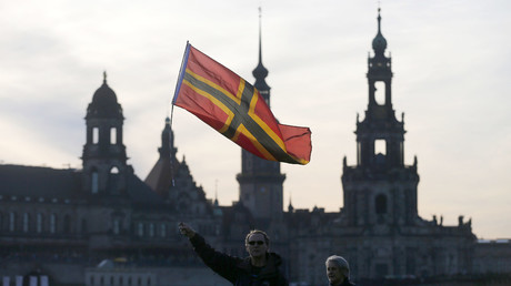 Supporters of the anti-Islam movement Patriotic Europeans Against the Islamisation of the West (Pegida) wave a flag during a demonstration in Dresden, Germany. © Hannibal Hanschke