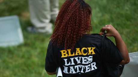 A woman wears a shirt with 'Black Lives Matter' during a memorial service for slain 18 year-old Michael Brown Jr. on August 9, 2015 at the Canfield Apartments in Ferguson, Missouri. © Michael B. Thomas