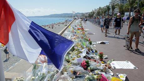 People walk past flowers left in tribute at a makeshift memorial to the victims of the Bastille Day truck attack near the Promenade des Anglais in Nice, France, July 21, 2016 © Jean-Pierre Amet