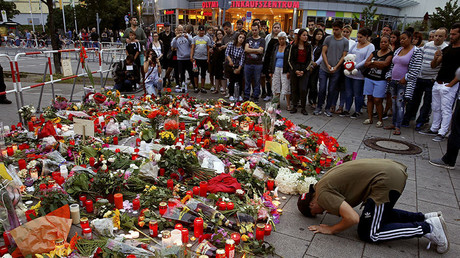 A man prays beside flowers laid in front of the Olympia shopping mall, Munich, Germany July 23, 2016. © Arnd Wiegmann