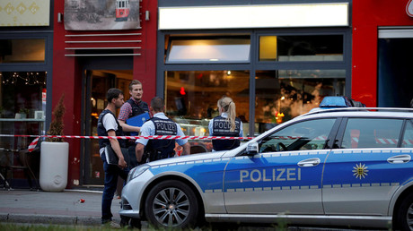 Police stand outside where a 21-year-old Syrian refugee killed a woman with a machete and injured two other people in the city of Reutlingen, Germany July 24, 2016. © Vincent Kessler