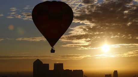 A hot air balloon rises into the early morning sky in front of the Canary Wharf financial district of London © Andrew Winning