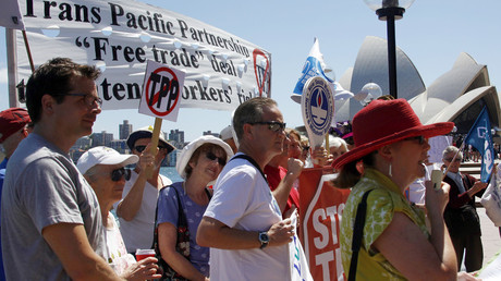 Protesters hold banners and signs in front of the Sydney Opera House during a demonstration against the Trans-Pacific Partnership (TPP) trade agreement. File photo. © David Gray