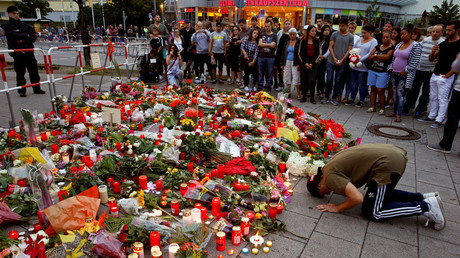 A man prays beside flowers laid in front of the Olympia shopping mall, where yesterday's shooting rampage started, in Munich, Germany July 23, 2016. © Arnd Wiegmann