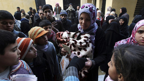 Residents queue to receive new and second-hand clothes as part of humanitarian aid at a school in Aleppo. File photo. © Muzaffar Salman