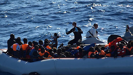 Migrants sit in their rubber dinghy during a rescue operation by Italian navy ship Borsini (unseen) off the coast of Sicily, Italy. © Marina Militare