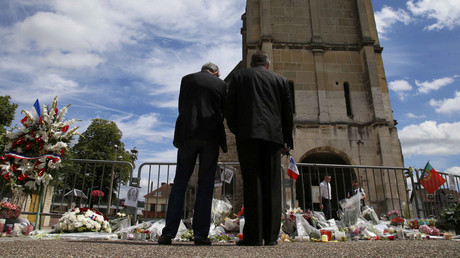 Men stand near flowers left in tribute to French priest Father Jacques Hamel outside the parish church at Saint-Etienne-du-Rouvray, near Rouen, France, July 28, 2016. © Pascal Rossignol