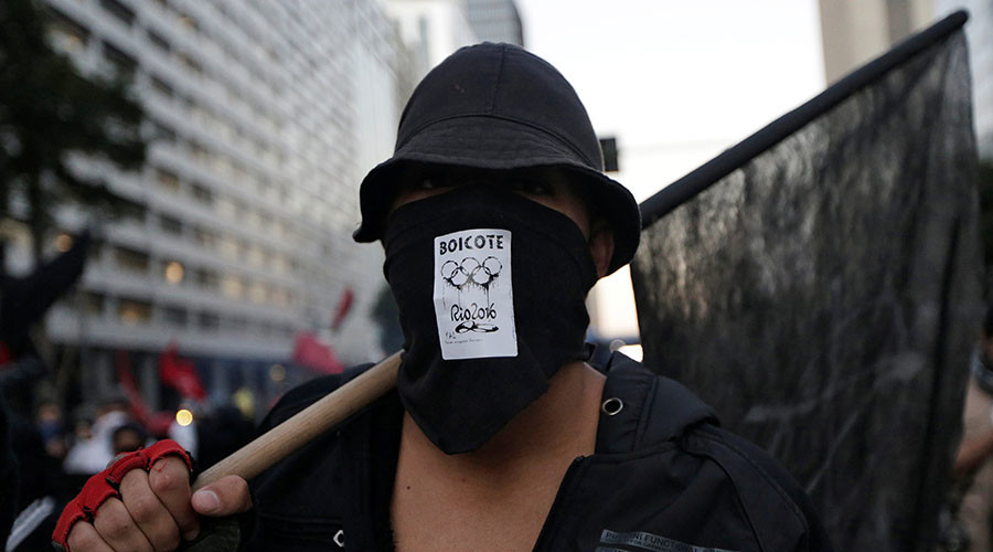 "An anti-government demonstrator, with a sticker which reads ""boycott"" on his mask, attends a protest on the Rio de Janeiro state economic crisis and against 2016 Rio Olympics in Rio de Janeiro, Brazil, July 6, 2016. © Ricardo Moraes"
