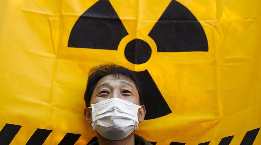 A man holds a flag with a radioactive hazard symbol during No Nukes Day, a protest calling for a nuclear-free future, in Yoyogi park in Tokyo, Japan. © Thomas Peter