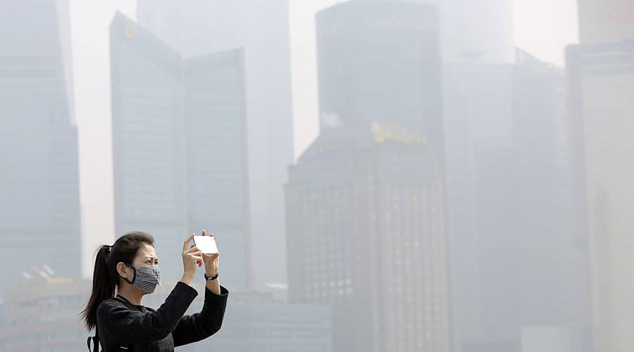 A woman wears a mask as she takes pictures on the Bund in Shanghai, China. © Aly Song