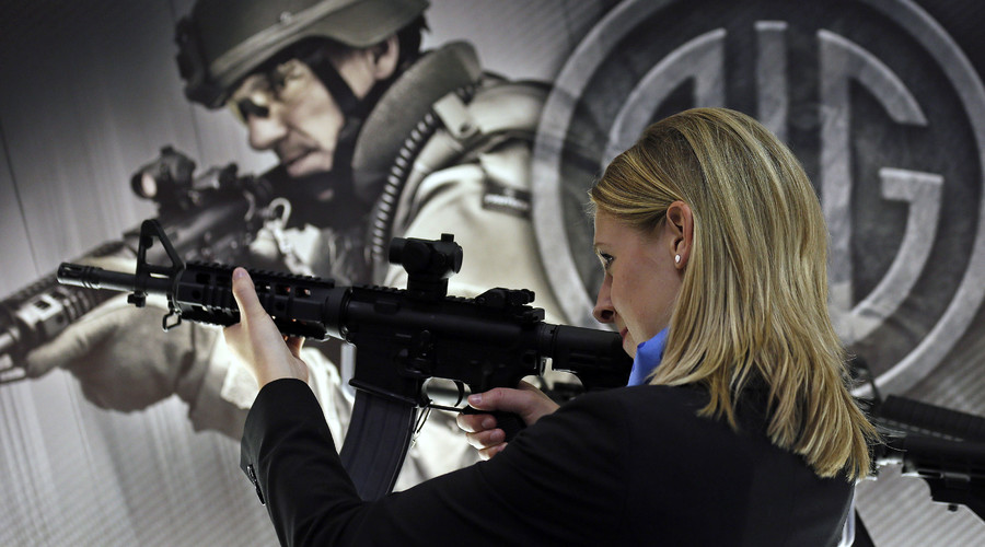 A woman aims a SIGM400 rifle during the Defence Security Equipment International (DSEI) arms fair at ExCel in London. File photo. © Stefan Wermuth