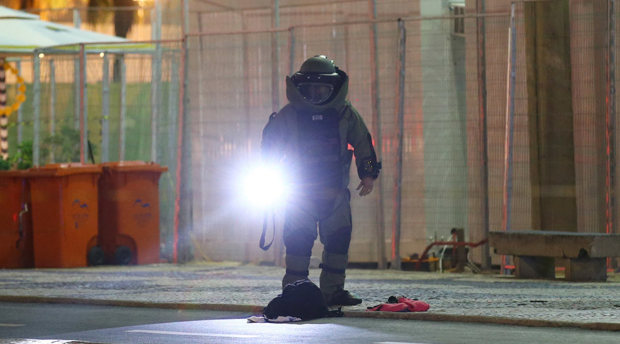 A bomb disposal expert wearing protective equipment examines a suspect package next to the beach volleball arena during the opening ceremony. © Carlos Barria