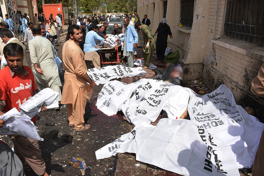 Pakistani volunteers move the body of a lawyer as others cover bodies after a bomb explosion at a government hospital premises in Quetta on August 8, 2016. © Banaras Khan