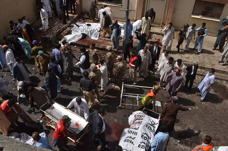Pakistani security officials and lawyers gather around the bodies of victims killed in a bomb explosion at a government hospital premises in Quetta on August 8, 2016. © Banaras Khan