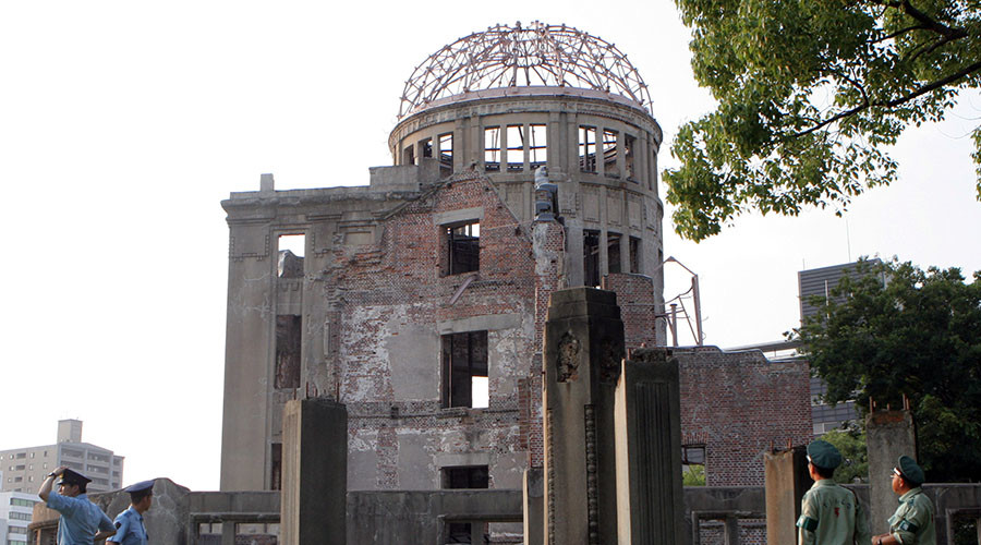 Guards stand near the gutted atomic bomb dome in the Peace Memorial Park in Hiroshima, Japan. © Toshiyuki Aizawa