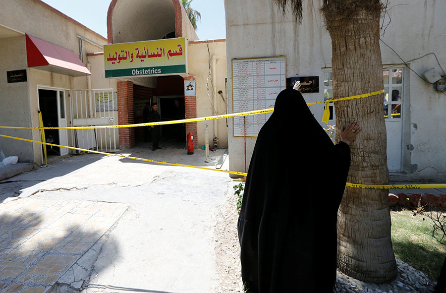 An Iraqi woman stands in front of a maternity ward after a fire broke out at Yarmouk hospital in Baghdad, Iraq, August 10, 2016. © Thaier Al-Sudani