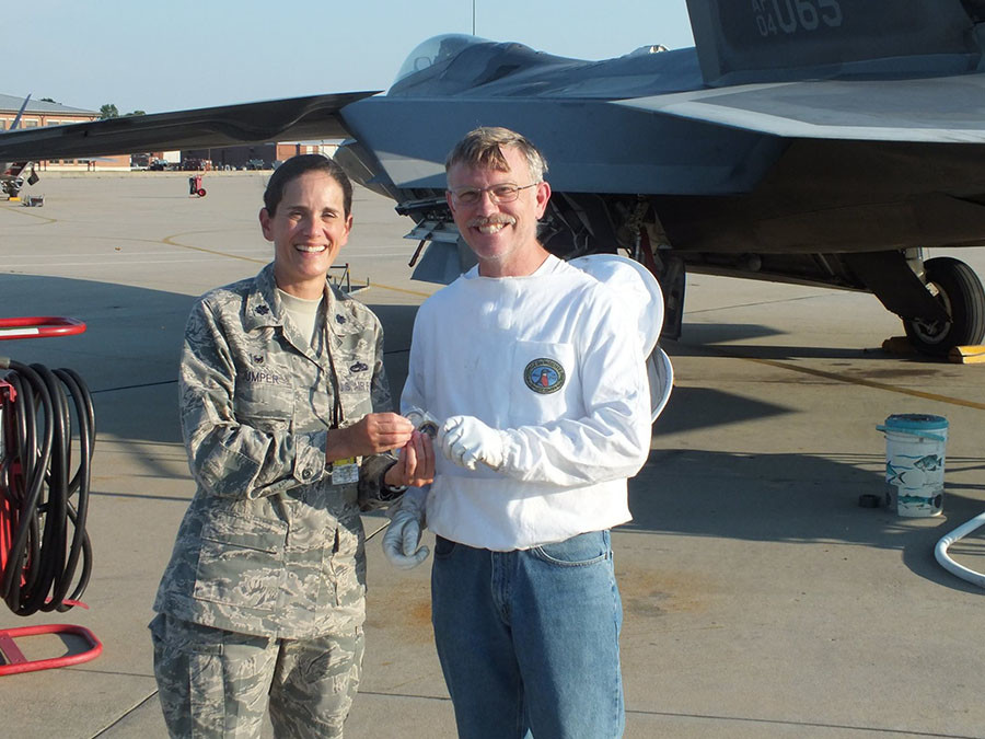 Lt. Col. Catherine M. Jumper, 192nd Aircraft Maintenance Squadron commander, presents beekeeper Andy Westrich with a coin on June 11, 2016 at Joint Base Langley-Eustis, Virginia. ©US Air Force