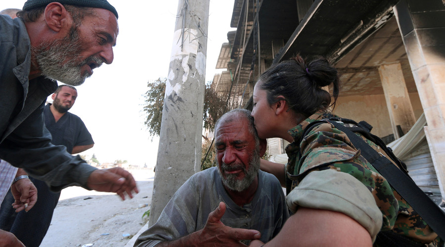 A Syria Democratic Forces (SDF) fighter comforts a civilian who was evacuated with others by the SDF from an Islamic State-controlled neighbourhood of Manbij, in Aleppo Governorate, Syria, August 12, 2016. © Rodi Said
