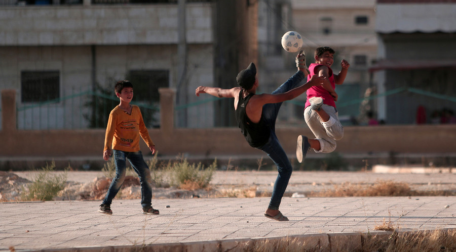 Youths play soccer on a street in Manbij, in Aleppo Governorate, Syria, August 9, 2016. © Rodi Said