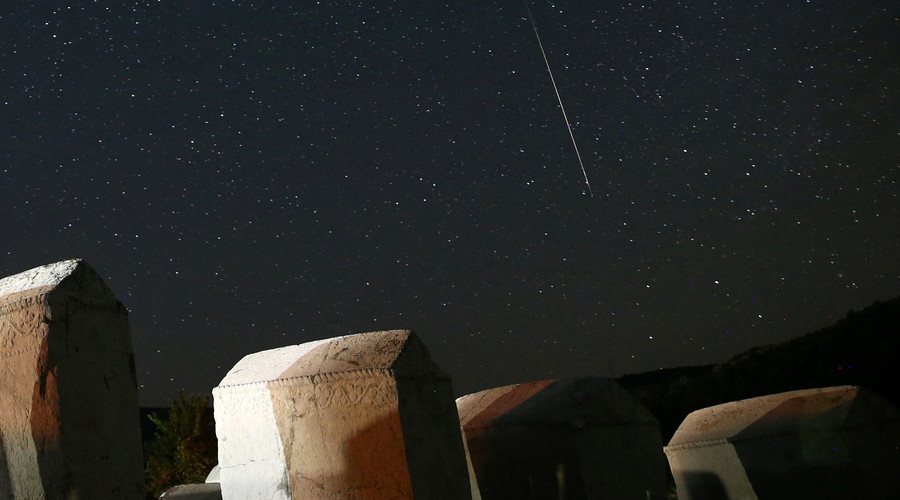 A meteor streaks past stars in the night sky above medieval tombstones in Radmilje near Stolac, south of Sarajevo, Bosnia and Herzegovina, August 12, 2016. © Dado Ruvic